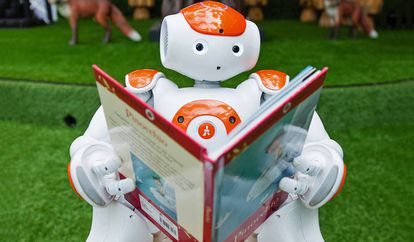 Un robot posa leyendo Pinocho en Westfield, Londres.