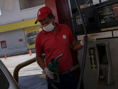 Un trabajador dispensa gasolina con guantes y mascarilla en Caracas el pasado 16 de marzo.