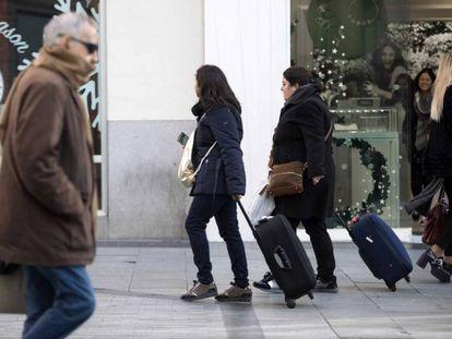 Dos turistas se dirigen a un piso turístico en el centro de la capital.