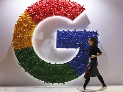 Una mujer pasa frente a un logotipo de Google en una feria de importación celebrada en Shanghái.