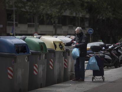 Un vecino de Barcelona tirando la basura en unos contenedores.