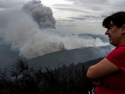 Una vecina de Ribas de Sil (Lugo) observa la columna de humo, este lunes.