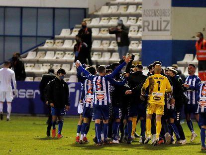 Los jugadores del Alcoyano celebran la clasificación, con los jugadores del Madrid al fondo abandonando el césped de El Collao. / (EFE)