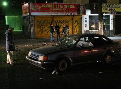 Un hombre observa un coche con agujeros de bala en el que se encontraron los cadáveres de dos policías el lunes en Tijuana.