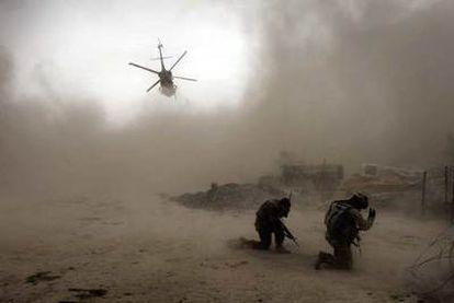 Soldados estadounidenses se protegen de la arena levantada por un helicóptero en Kandahar.