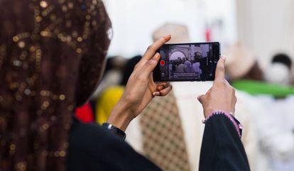Una mujer hace fotografías con su 'smartphone' durante las fiestas Maulidi en Kenia.