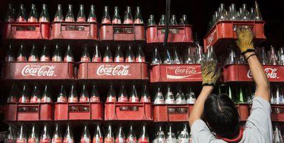 Un trabajador apila cajas vacías de botellas de Coca-Cola en México.