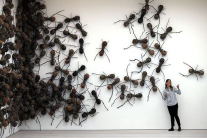 Una visitante posa junto a la obra 'Casa Tomada', de Rafael Gomezbarros, en la muestra 'Pangaea: Arte Nuevo de África y América Latina' en la galería Saatchi de Londres.