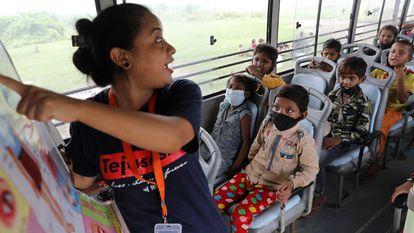Una profesora enseña a un grupo de estudiantes dentro de un autobús en Nueva Delhi, India, el 9 de agosto de 2021.