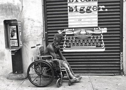 Un indigente en silla de ruedas mira al fotógrafo en una calle de Skid Row.