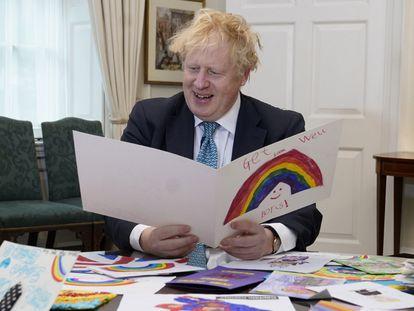 Boris Johnson observa los dibujos enviados por los niños durante su estancia en un hospital a causa del coronavirus.