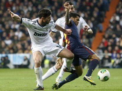 Alves protege el balón entre Xabi y Arbeloa.