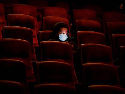 Una persona usa su teléfono móvil en el cine AMC casi vacío, mientras esperan la primera proyección el día de ayer en Burbank, California.
