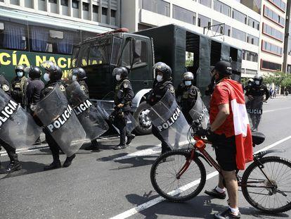 Un ciclista pasa delante de un grupo de Policías en Lima tras la renuncia de Manuel Merino a la Presidencia de Perú.