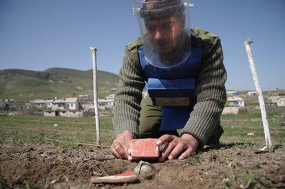 Un empleado de HALO manipula con cuidado munición procedente de una bomba de racimo