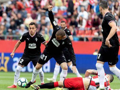 El centrocampista del Girona David Timor pelea el balón con los jugadores del Eibar Enrique García, Pedro León y Fabián Orellana.