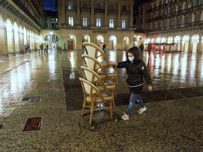 Una operaria recoge unas sillas este lunes en la Plaza Constitución de San Sebastián.