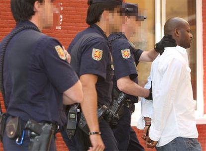 La policía trasladaba ayer a uno de los detenidos durante la operación desarrollada en Málaga.