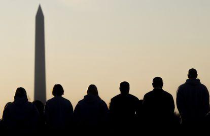 Un grupo de hombres y mujeres observa el obelisco de Washington.