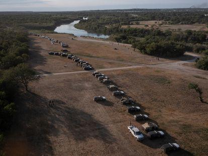 Vehículos militares y de las fuerzas del orden crean un cordón alrededor de los migrantes que se refugian en un campamento fronterizo improvisado en Del Rio, Texas.