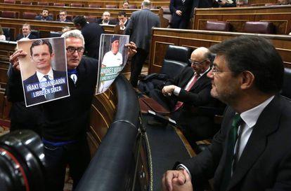 Diego Cañamero muestra dos fotos a Rafael Catalá, el pasado marzo en el Congreso.