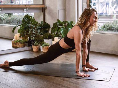 Una mujer práctica yoga, un ejercicio ideal para relajarse del estrés y la ansiedad.