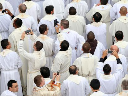 Sacerdotes sacan fotos con sus móviles durante la misa oficiada por el papa Francisco antes de la apertura de la Puerta Santa en 2019.