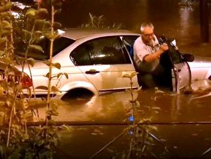 Un hombre, obligado a abandonar su vehículo a causa de un embalsamiento, anoche en Madrid.