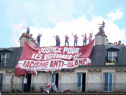 """Activistas de extrema derecha deslizan una pancarta que pide justicia para las """"víctimas del racismo anti-blanco"""" en una azotea de París el 13 de junio de 2020."""