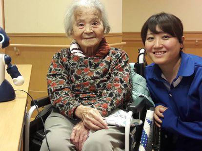 Una mujer japonesa de avanzada edad, junto a una cuidadora y el robot 'Sota', en una residencia de Tokio.