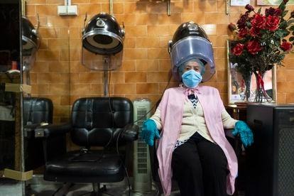 Las escenas de la nueva normalidad. Una clienta en la peluquería de Maribel de Lavapiés, en el día de reapertura de estos locales tras el confinamiento.