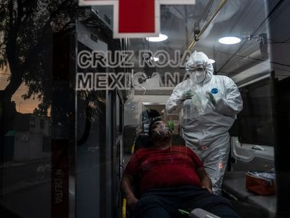 Un paramédico de Cruz Roja estabiliza en la ambulancia a un hombre en situación grave por covid-19.