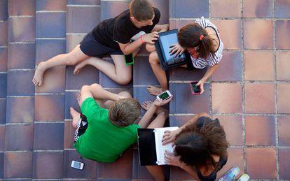 Niños y niñas con ordenadores y dispositivos electrónicos.