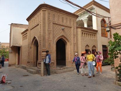 Un grupo de turistas chinos pasa junto a una mezquita clausurada en la ciudad antigua de Kashgar.