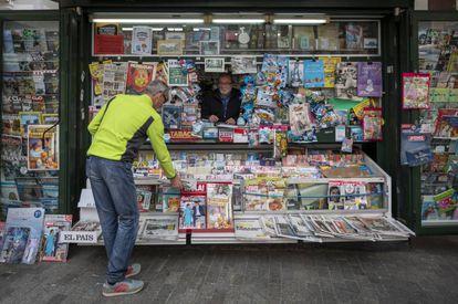 Un hombre compra  el periódico en un quiosco de Valencia, este martes.
