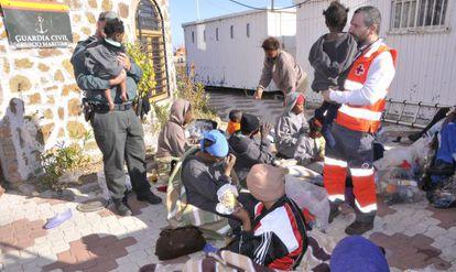 Guardia Civil y Cruz Roja atendiendo a algunos de los 45 inmigrantes llegados a Ceuta.