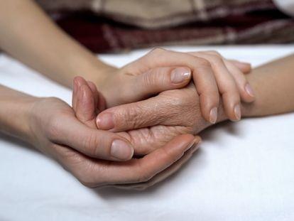 Una mujer le coge la mano a otra, en una foto de archivo.