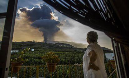 Una mujer contempla la columna de humo lanzada por el volcán de La Palma, este jueves.