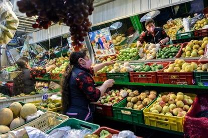 Una mujer con mascarilla acomoda frutas en su puesto del mercado en Corabastos el 27 de julio de 2020, en Bogotá, Colombia.
