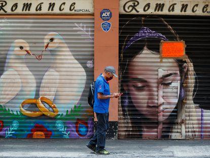 Un hombre camina frente a dos locales cerrados en Ciudad de México.