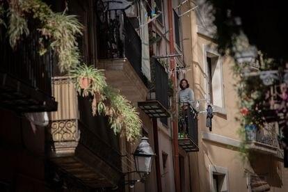 Un hombre se asoma al balcón durante el estado de alarma por coronavirus, en Barcelona.