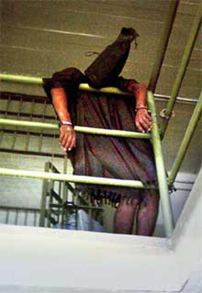 Esta otra imágen muestra a un preso iraquí con un capuchón en la cabeza y esposado a una barrotes de la prisión de Abu Ghraib.