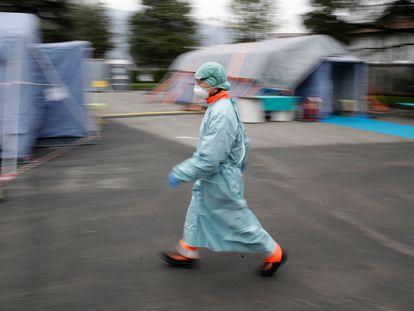 Un trabajador sanitario camina entre las instalaciones de emergencia instaladas en Brescia, al norte de Italia.