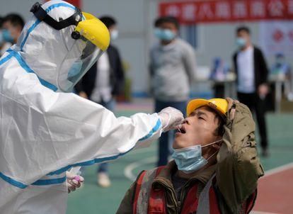 Personal sanitario efectúa la prueba del coronavirus a un trabajador en Wuhan