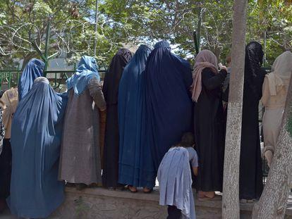 Mujeres afganas que han huido del avance de los talibanes esperan para recibir comida de beneficencia en un parque de Kabul, el viernes.