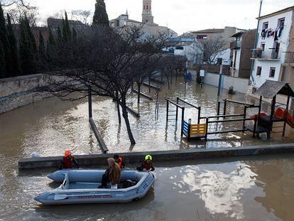Personal de Protección Civil desalojan a una mujer durante las fuertes inundaciones en Tudela por la crecida del río Ebro.