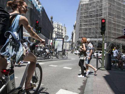 Una mujer con una bicicleta del servicio público de alquiler BiciMad.
