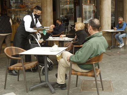Un camarero atiende a varios clientes en la terraza de un bar en Palma (Baleares), a primeros de marzo.