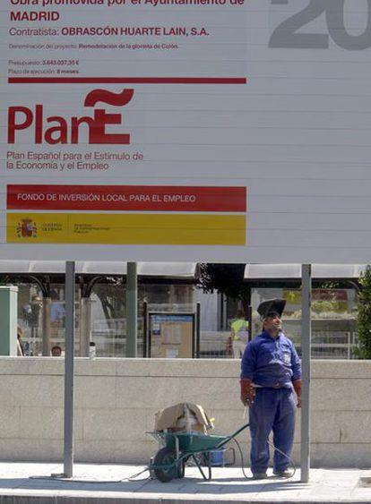 Un trabajador de la construcción, ante un cartel del Plan E situado en una obra de Madrid.
