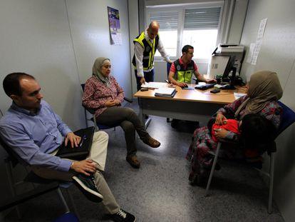 Una mujer siria (derecha) solicita asilo en Melilla tras cruzar la frontera con Marruecos.